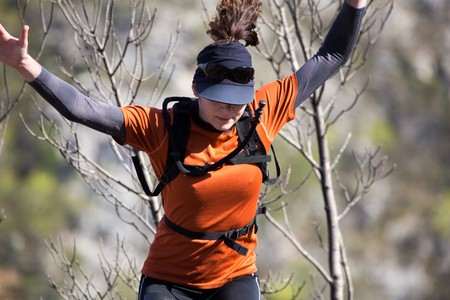 A woman hiker in sports clothing and sports equipment jumping with her arms raised. National park Paklenica, the part of Velebit; the largest mountain range in Croatia. Stock Photo