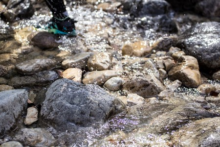Hiker uses stepping stones to cross stream. National park Paklenica, the part of Velebit; the largest mountain range in Croatia.