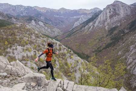 A woman in sports clothing running through the rocky mountains. National park Paklenica, the part of Velebit; the largest mountain range in Croatia.