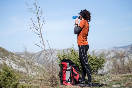 Woman hiker taking break and drinking water. National park Paklenica, the part of Velebit; the largest mountain range in Croatia.