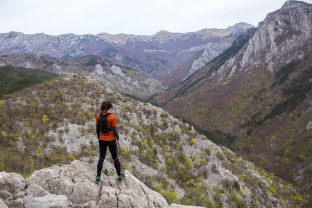A woman in sports clothing and sports equipment standing and watching the rocky mountains. National park Paklenica, the part of Velebit, the largest mountain range in Croatia.