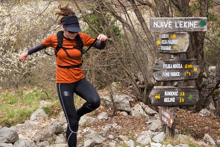 A woman in sports clothing jumping in the forest. National park Paklenica, the part of Velebit; the largest mountain range in Croatia.
