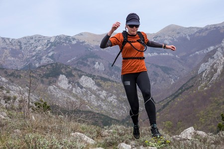 A woman in sports clothing jumping through the rocky mountains. National park Paklenica, the part of Velebit; the largest mountain range in Croatia. Stock Photo