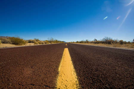 Low perspective as the roads yellow divider line heads off in the distance. Shot in the deserts of Arizona. Stock Photo