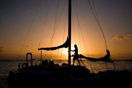 Silhouette of a man standing in his sailboat at sunset. Shot at Waikiki beach in Hololulu, Hawaii.