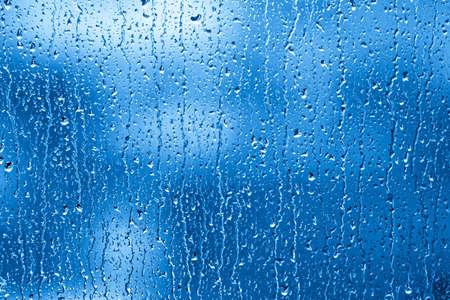 Regendruppels zijn het verzamelen en streaming in een venster. Stockfoto