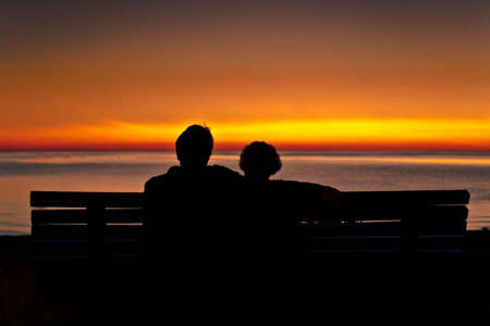 A romantic couple are watching the sunset over the ocean.