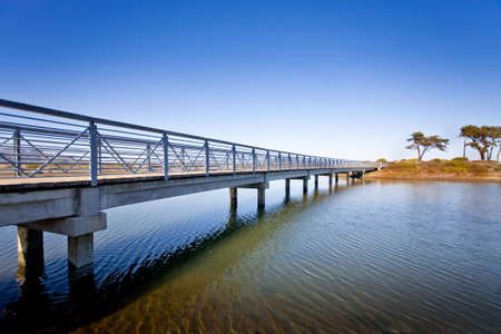 A bridge spans across the water leading to an island.