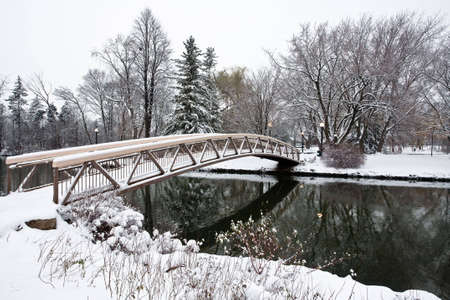 Winter scenic of a small bridge crossing over a river in a park.
