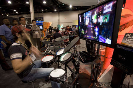 LAS VEGAS - JANUARY 8, 2009: An enthusiastic gamer playing Guitar Hero World Tour on a Roland Drumset at the 2009 Consumer Electronic Show held in Las Vegas, Nevada, on January 8, 2009. Stock Photo - 6884696