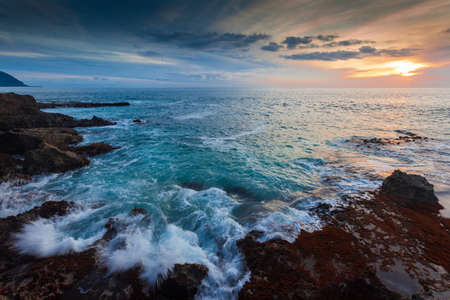 hawaii sunset: Waves are splashing up on the shores at Kaena Point in Hawaii. Shot at dusk. Stock Photo