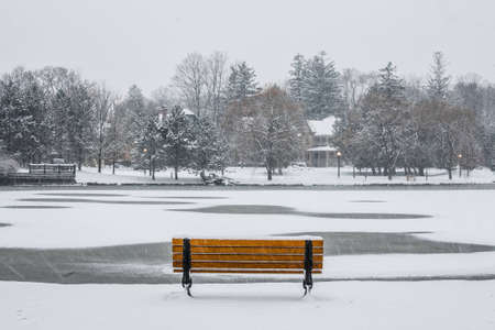 A park bench overlooks the snow covered pond.