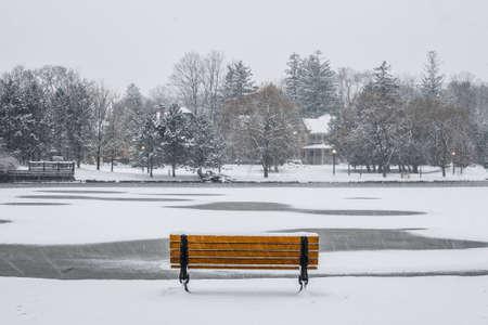 Een bankje in het park met uitzicht op de met sneeuw bedekte vijver.