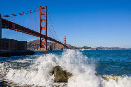 Waves crash on the shore in front of the Golden Gate Bridge in San Francisco, California