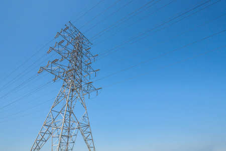 A single hydro towers stands tall against a blue sky