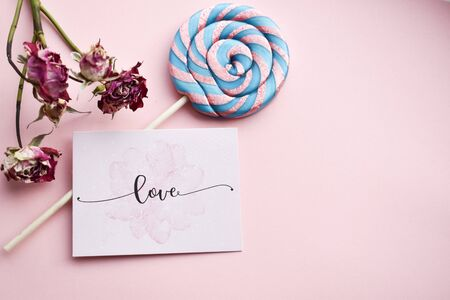 Purple-pink spiral Lollipop on white background and sticker with the inscription love, a place for text Banco de Imagens