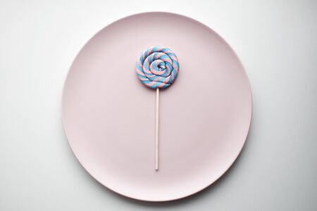 Purple-pink spiral Lollipop on white background, a place for text