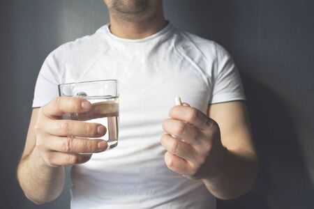 In the man's hand are medicinal tablets and a glass of water. Healthcare, the concept of medical supplements