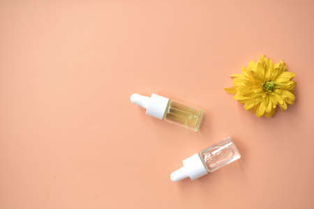 Cosmetic oil in a bottle with a pipette for the face and body on a natural background with a decor in the form of a natural stone. Space for text.