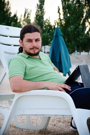 een man zit op de stoel met de laptop Stockfoto