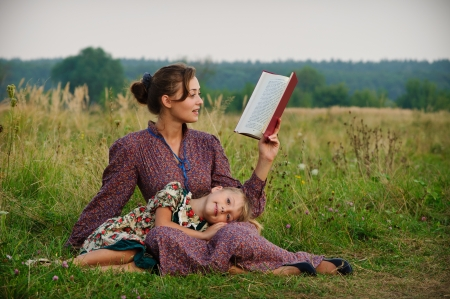 children reading books: Mother and daughter sitting on the grass, and the girl put her head on her mother on her knees and her mother is reading a book