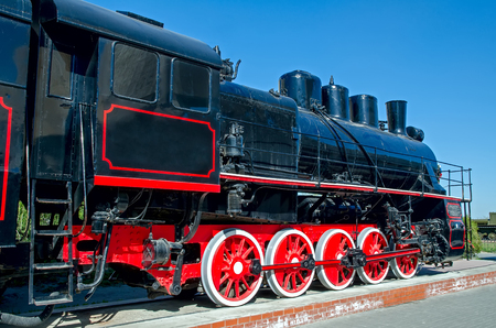 Old Russian (Soviet) steam locomotive on a pedestal on a background of blue sky Banco de Imagens - 102297010
