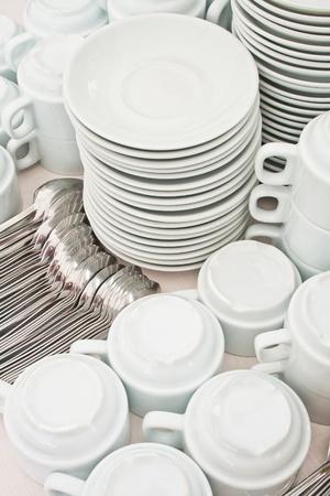 pile wihte tea tableware and spoons photo