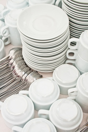 catering table: pile wihte tea tableware and spoons