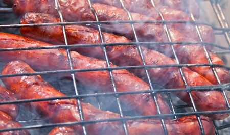 grill sousage on barbecue grid in smoke
