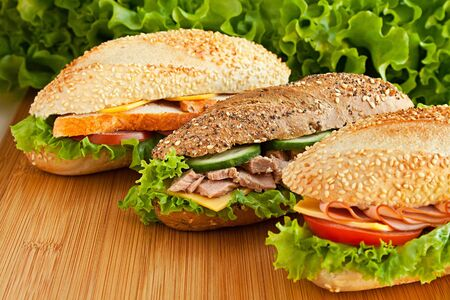 three different sandwich on wood