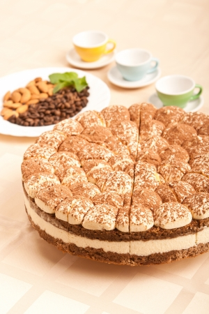 sweet tiramisu cake with almonds, coffee beans and cups Stock Photo