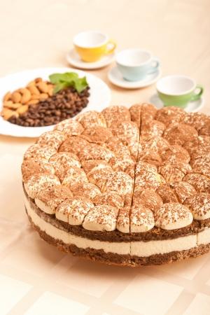 sweet tiramisu cake with almonds, coffee beans and cups Stock Photo