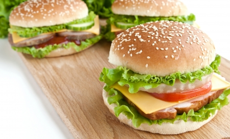 chicken burger: three hamburger with meat and vegetables on wood plate Stock Photo