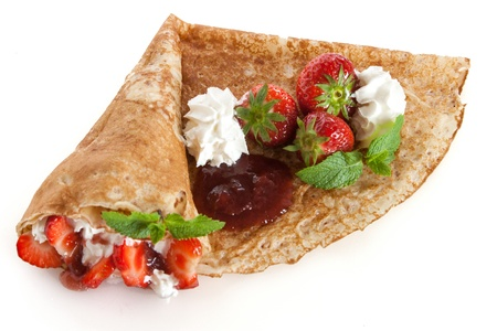 Rolled thin pancakes with strawberry, sweet cream and mint