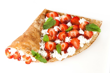 Rolled thin pancakes with strawberry, sweet cream and mint photo