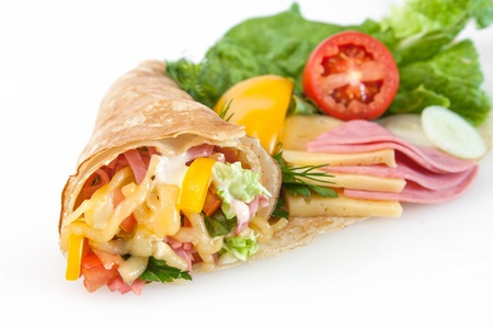 Rolled thin pancakes with ham, cheese and vegetables