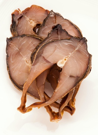 sliced smoked fish on plate on white background