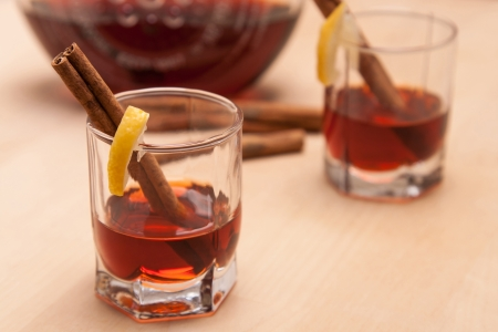 cannelle: glass heating red liqueur with cinnamon sticks on wood table