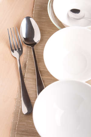 white bowls and silverware on napkin and wood background