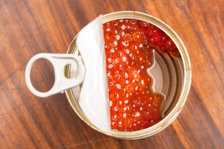 red caviar in bank with spoon on wood background photo