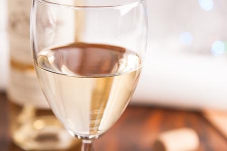 бокал и бутылка белого вина на мигают светлом фоне