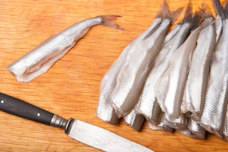 smelt: many uncooked trunk small fish on wood board Stock Photo