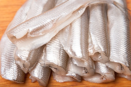 many uncooked trunk small fish on wood board Stock Photo - 17316378