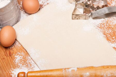 pastry, rolling pin, eggs and figures for cookies on wooden photo