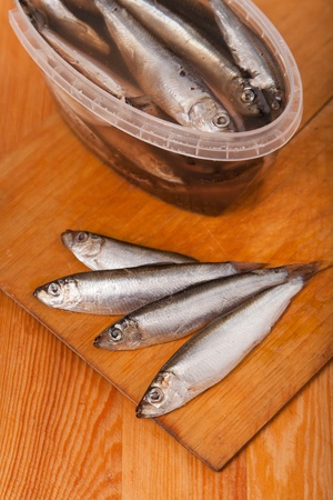 forage fish: salted anchovies in box on wooden background