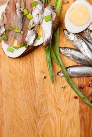 sprat: sandwich from salted anchovies with egg and spring onion on wood Stock Photo