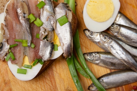 forage fish: sandwich from salted anchovies with egg and spring onion on wood Stock Photo