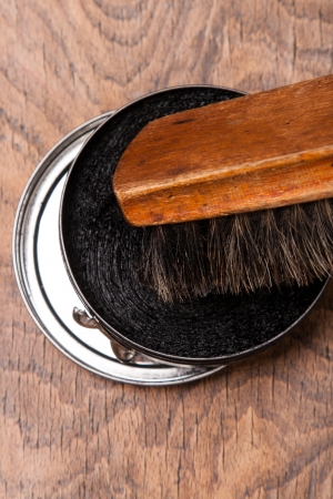 blacking: container of shoe polish and brush on wooden background  Stock Photo