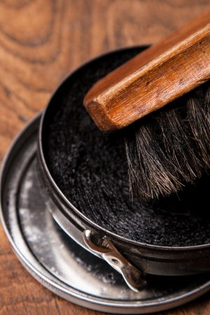 container of shoe polish and brush on wooden background  Stock Photo