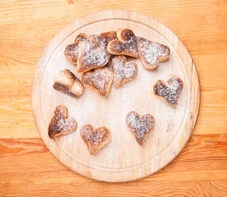 bakery hearts from split pastry with sugar powder on wooden board Stock Photo - 17855251